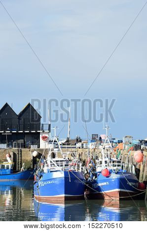 Whitstable United Kingdom -October 1 2016: Fishing Boats in Whitstable Harbour in portrait view with warehouse in background