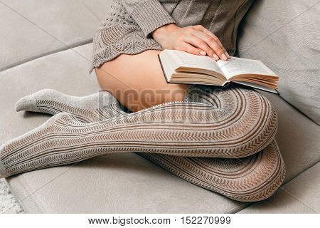Young beautiful woman in a knitted sweater and stockings reading a book sitting on the couch