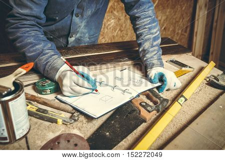 Man carpenter in his home studio working with wood and draws sketches in pencil in a notebook