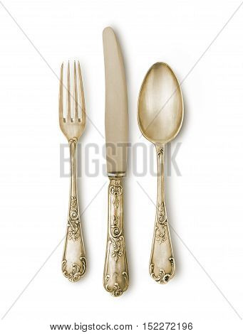 Golden cutlery set against white background with a soft shadow. Pieces with ancient marks and texture. Clipping path