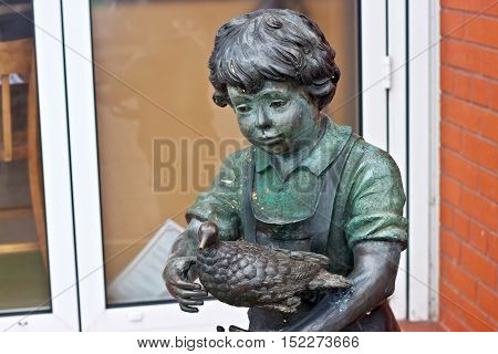 RUSSIA ZELENOGRADSK - OCTOBER 11 2014: Sculpture of a boy with bird in the Zelenogradsk promenade. Zelenogradsk (Cranz) is a resort town in Kaliningrad Oblast Russia near the Curonian Spit on the Baltic Sea.