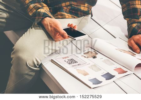 Man shopping scanning qr code advertising with smartphone on clothes catalog modern technology and fashion retail concept poster