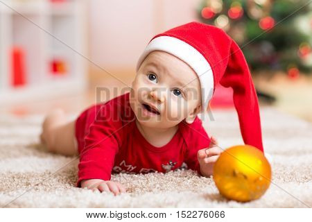 Funny baby wearing Santa hat and suit. Kid boy lying on tummy in front of Christmas tree at home