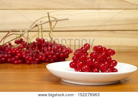 Red berries and viburnum branches with berries lie on a wooden table