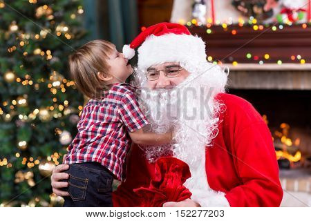 Santa Claus and child with presents at fireplace. Kid boy and father in Santa costume and beard