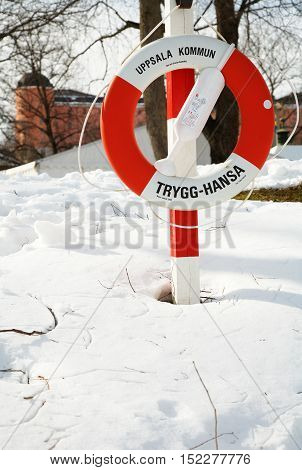 Uppsala Sweden - March 23, 2006: A lifebuoy in winter environment from the insurance company Trygg-Hansa with the Uppsala castle in the background.