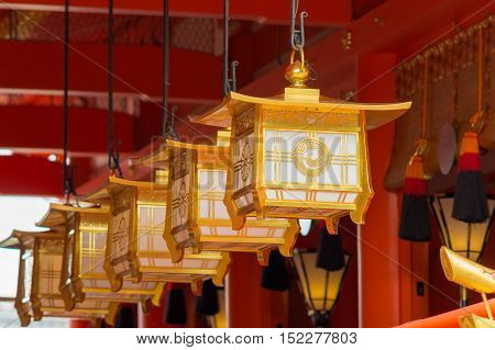Kyoto Japan - September 17 2016: Fushimi Inari Taisha Shinto Shrine. Closeup of a line of golden lanterns hanging off the vermilion ceiling in front of the idols.