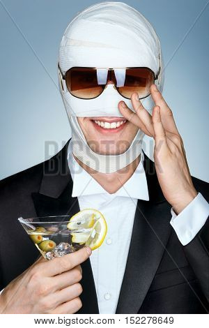 Beauty victim with bandage on his face after facelift. Glamorous man in sunglasses and with glass of martini cocktail. Plastic Surgery concept.
