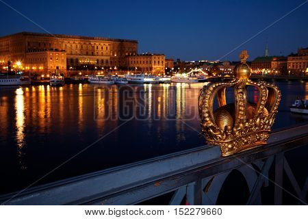 Stockholm, Sweden - November 10, 2012: Royal crown on the railing of the bridge to Skeppsholmen the royal palace in the background.
