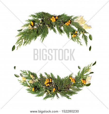 Christmas concept - frame wreath with evergreen Cupressus nootkatensis and Pyracantha red and yellow berries. Flat lay top view.