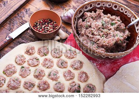 Prepare raw homemade food - dumpling in metal strainer pelmennica. They have a traditional form. Pork chicken mincemeat. Background is red.