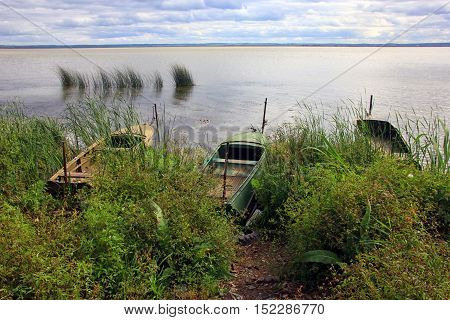 three old metal boats at the shore of a large lake Nero in summer and the reeds in the water