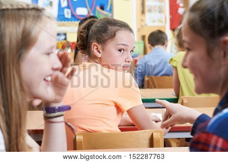 Unhappy Girl Being Gossiped About By School Friends In Classroom
