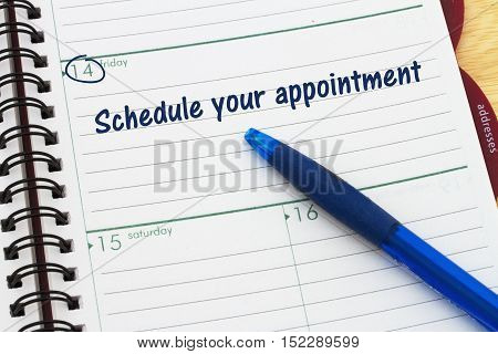 Reminder to schedule your appointment A day planner with blue pen with text Schedule your appointment