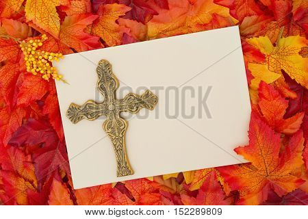 An inspirational message Some fall leaves with a blank beige greeting card with a cross with copy-space for your message