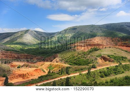 Beauitful landscape of mountain opencast mine in sunny summer day under blue cloudy sky with road passes through.