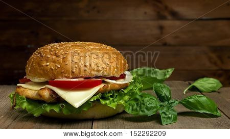 Home made hamburger with cheese, tomatoes and basil  on wooden background. Fastfood meal.