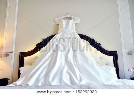 Beautiful white wedding dress for bride indoors on the bed. Beauty of bridal gown for marriage. Female lace clothes for celebration
