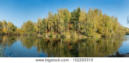 Pond in a forest in autumn. Panoramic image from several pictures.