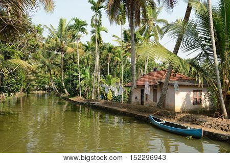 India Coco trees reflection and beautifoull house boat at back waters of Kerala