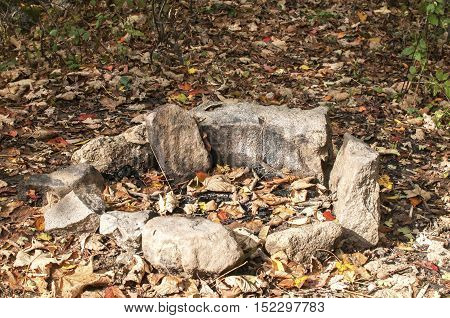 Manmade stone unlit open fireplace in nature in autumn