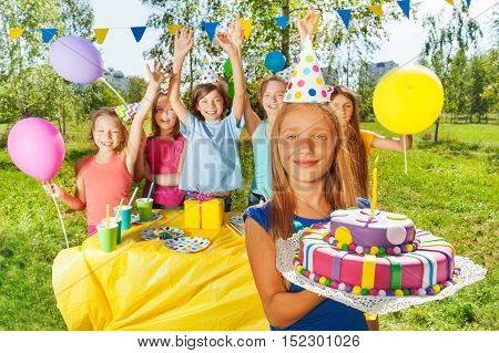 Happy young girl holding majestic icing birthday cake with burning candle stick on it