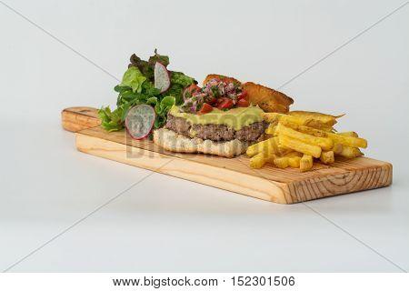burger with guacamole sauce tomato lettuce and chips in foccacia bread
