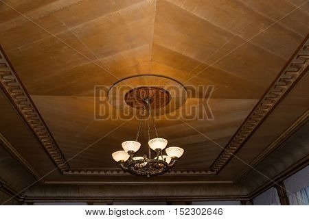 Beautiful Chandelier On The Background Of Wooden Ceiling.