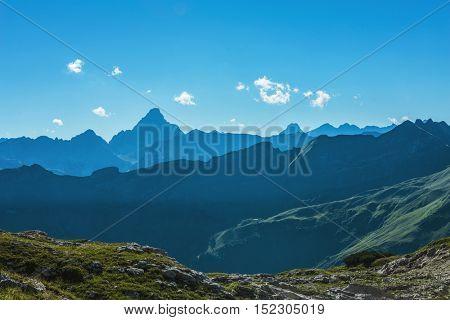 Grosser Daumen Alps mountain range with deep dark valley in foreground with copy space