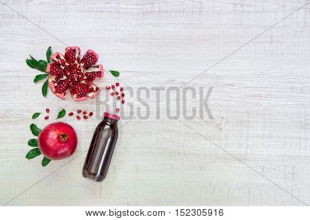 Left bottle of pomegranate juice near pomegranate pomegranate slices seeds on a light white wood background right empty space. Bottle of pomegranate juice and pomegranates. Horizontal. Top view.