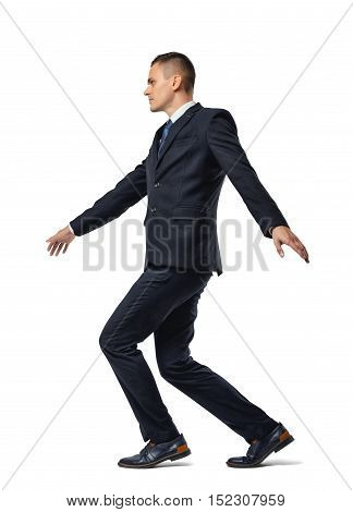 Full growth portrait of a businessman walking a tightrope isolated on a white background. Keeping balance. Acting carefully. Being very cautious.