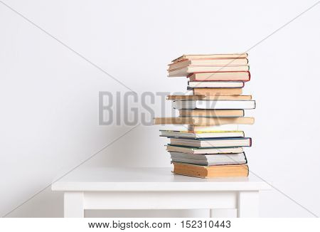 Stack of hardback books on the white table on white wall background. Search for relevant and necessary information in a large number of sources during studies or work
