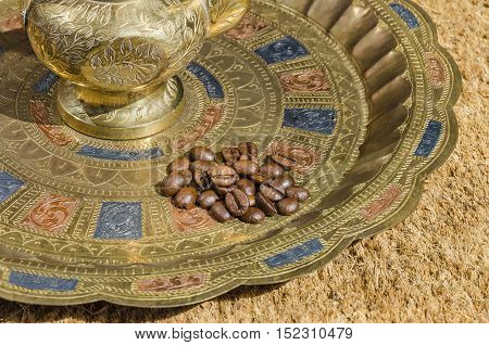 Small heap of Coffee beans on an engraved ( embossed) plate with an engraved metallic coffeepot designed specifically for making Arabic coffee