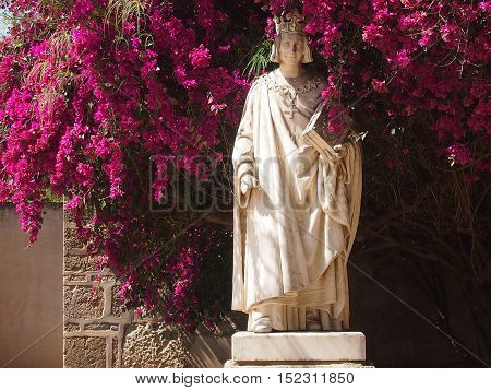 Marble statue among bushes of the blossoming azalea