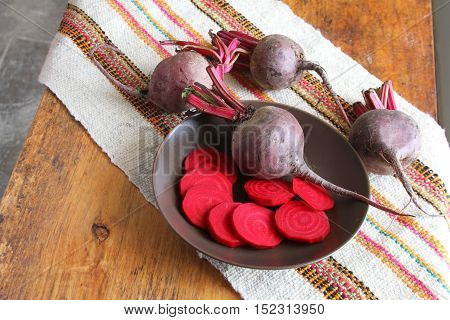 Bowl of whole and sliced beets on a table with colorful place mat in Peru