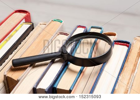 Stack of old hardback books with magnifying glass. Search for relevant and necessary information in a large number of sources during studies or work