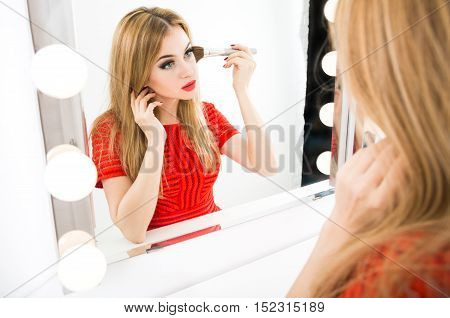 Beautiful Woman Applying Makeup Powder with a Big Brush and Reflected in the Mirror. Fashion Make Up Concept.