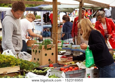 Södertälje, Sweden - July 16, 2012: Farmers markets  in the main square. Customers seen searching among the supply of vegetables.