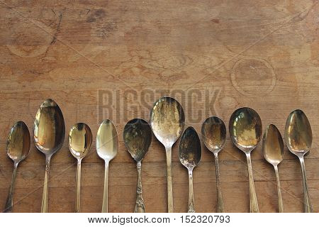 Over head flat lay view of a collection of silver tarnished spoons side by side against a rustic wood table