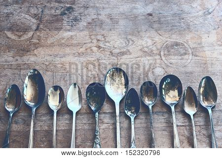 Over head flat lay view of silver tarnished spoons side by side against a rustic wood table