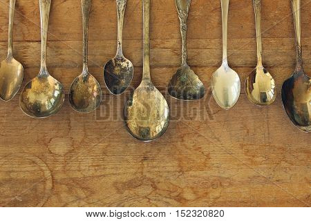 Over head flat lay of an assortment of vintage tarnished spoons