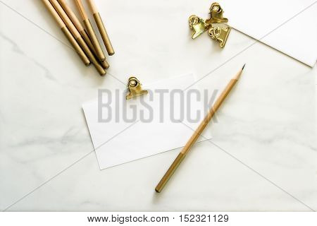 Over head flat lay desktop with gold office supplies and blank notecard for copy or text