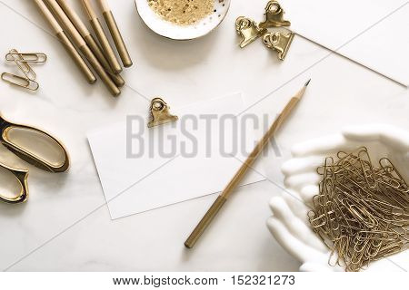 Over head flat lay view of gold office supplies against white background with blank notecard for text