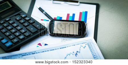 Business of financial analysis of workplace. calculator, mobile phone and pen on financial chart