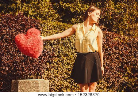 Love romance heartbreak sadness concept. Girl throwing heart into dumpster. Young lady holding plush love symbol over bin.