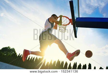 Street Basketball Player Performing Power Slum Dunk.