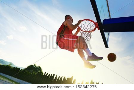 Young Basketball Player Drives To The Hoop For A High Flying Slam Dunk In Front Of Sunset Sky.