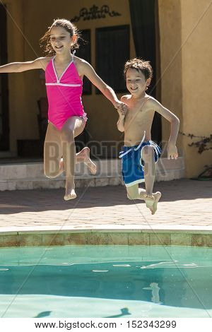 Two children boy and girl laughing having fun jumping into swimming pool