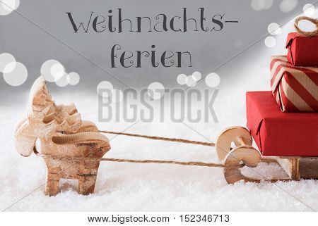 Moose Is Drawing A Sled With Red Gifts Or Presents In Snow. Christmas Card For Seasons Greetings. Silver Background With Bokeh Effect. German Text Weihnachtsferien Means Christmas Break