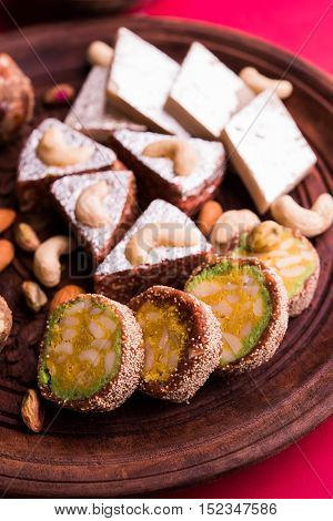 Indian sweet dry fruits and nuts barfi or burfi or laddu, which is a traditional, healthy, nutritious and popular dish, is made from items like dates, raisins, almonds, cashew nuts, flaxseeds & anjeer